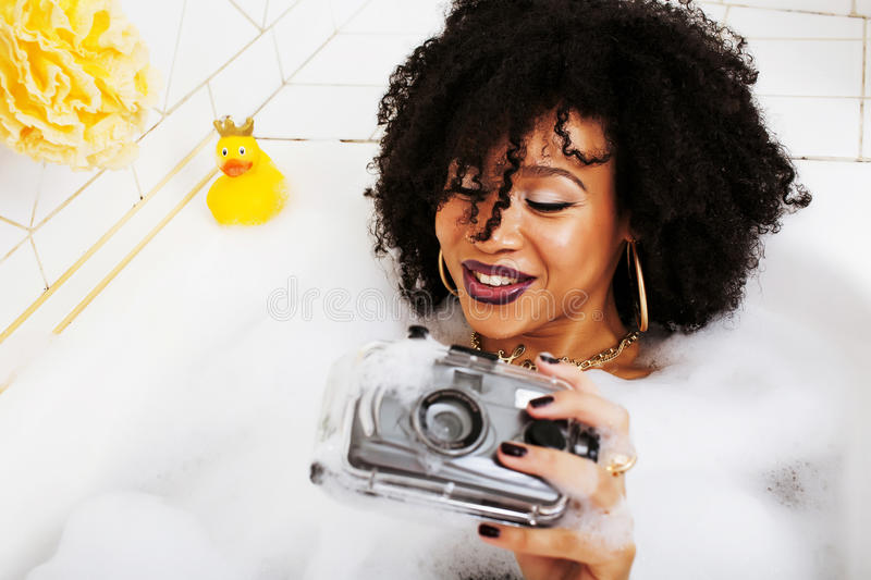 Young afro-american teen girl laying in bath with foam, wearing. Swag jewelry flawless, making selfie close up royalty free stock photo