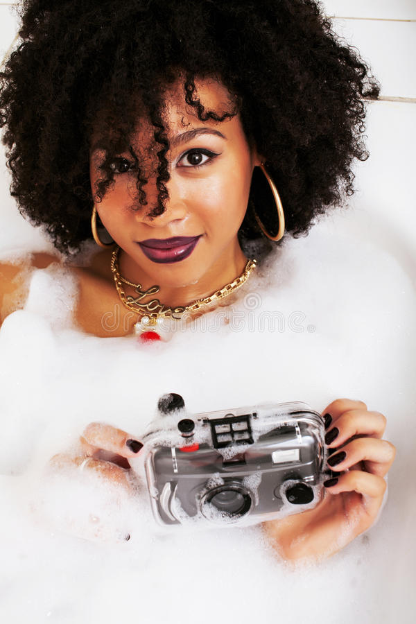Young afro-american teen girl laying in bath with foam, wearing. Swag jewelry flawless, making selfie close up royalty free stock photos