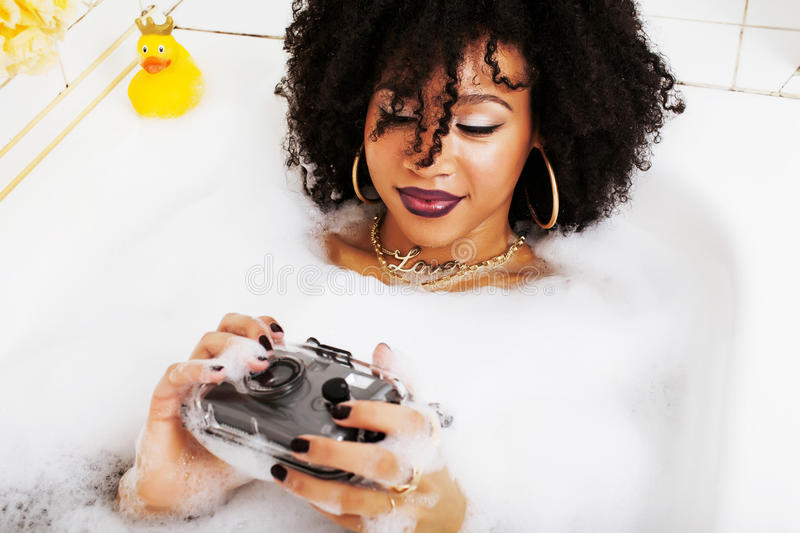 Young afro-american teen girl laying in bath with foam, wearing. Swag jewelry flawless, making selfie close up stock images