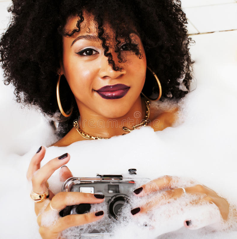 Young afro-american teen girl laying in bath with foam, wearing. Swag jewelry flawless, making selfie, modern lifestyle concept, spa woman stock photo