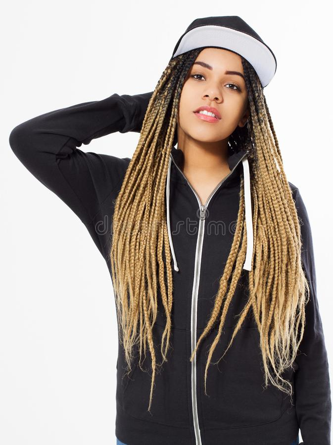 Young afro american woman in a baseball cap and a black hoodie is on a blue background,hipster stock photo