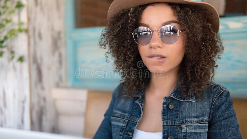 Young Afro-American woman in glasses and hat biting a lip, wearing jeans jacket royalty free stock photo