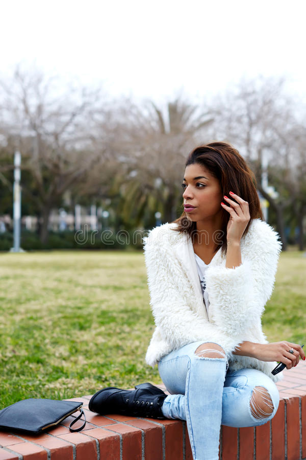 Young afro american woman sitting in beautiful park looking away stock photos