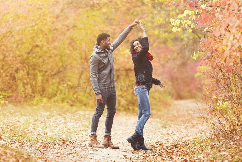 Young afro couple dancing in autumn park, having fun stock photos