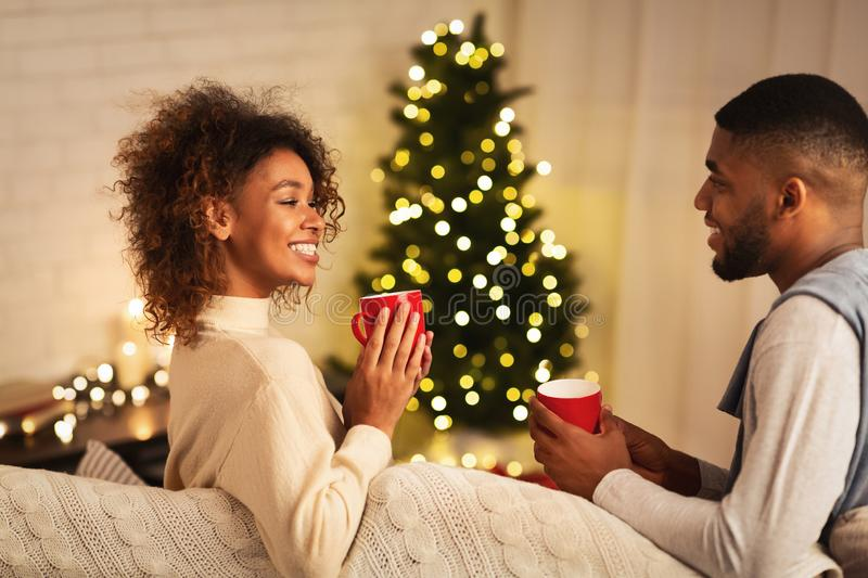 Young afro couple drinking cocoa in front of Christmas tree stock photography