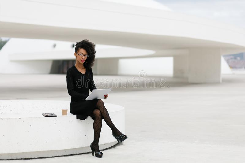 Stylish young afro hair professional woman using tablet royalty free stock photo