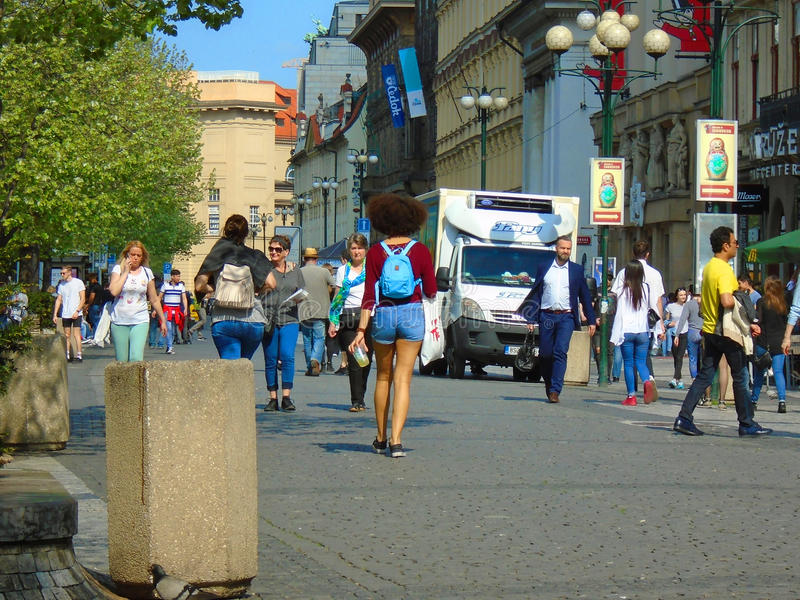 Young Afro woman from behind on the square full of people.Prague, Czech Republic, stock image