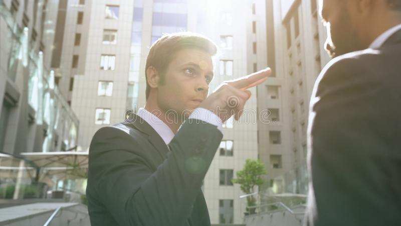 Young aggressive businessman making watching you gesture to employee, boss royalty free stock images