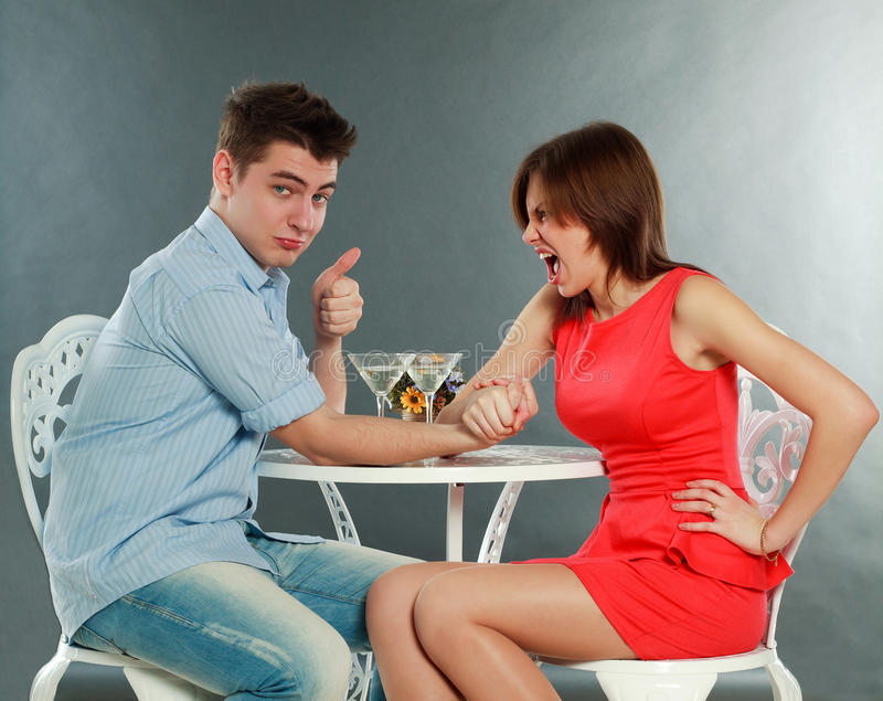Young aggressive woman winning fighting in arm-wrestling. Young aggressive women winning fighting in arm-wrestling at table, in studio isolated on gray royalty free stock photos
