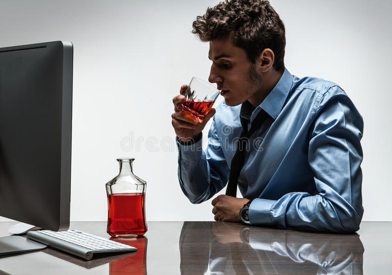 Young alcoholic man drinking whiskey sitting drunk at office with computer. Photo of businessman addicted to alcohol at the workplace, depression and crisis stock photo