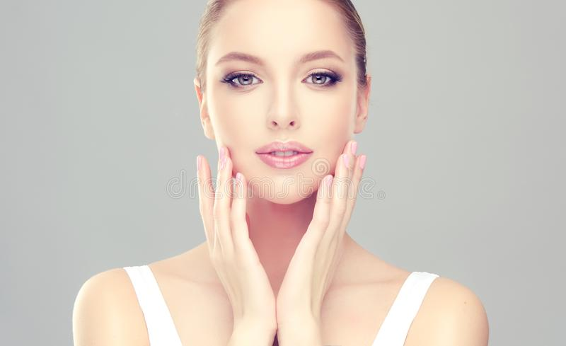 Alluring woman with clean fresh skin is touching the face tenderly. Young, alluring woman with clean fresh skin and soft, delicate make up is touching the face stock photography