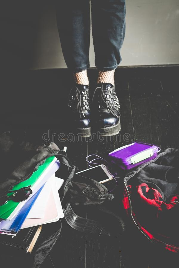 Young alternative girl on the black floor with a school bag. Young alternative girl standing on the black floor with a school bag, smartphone, sunglasses and stock photos