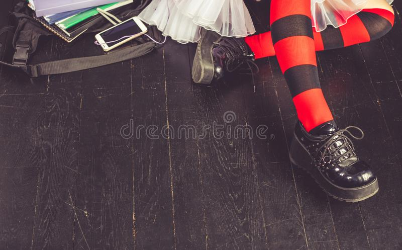 Young alternative girl with school bag on the wooden floor. Young alternative girl sitting on the black floor with a school bag, smartphone, sunglasses and stock photography