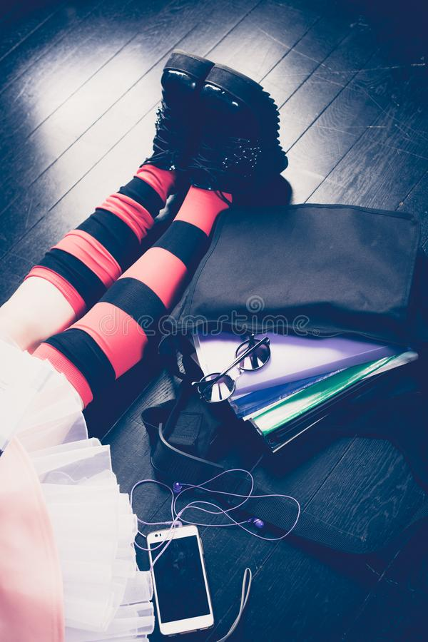 Young alternative girl with school bag on the wooden floor. Young alternative girl sitting on the black floor with a school bag, smartphone, sunglasses and stock photo