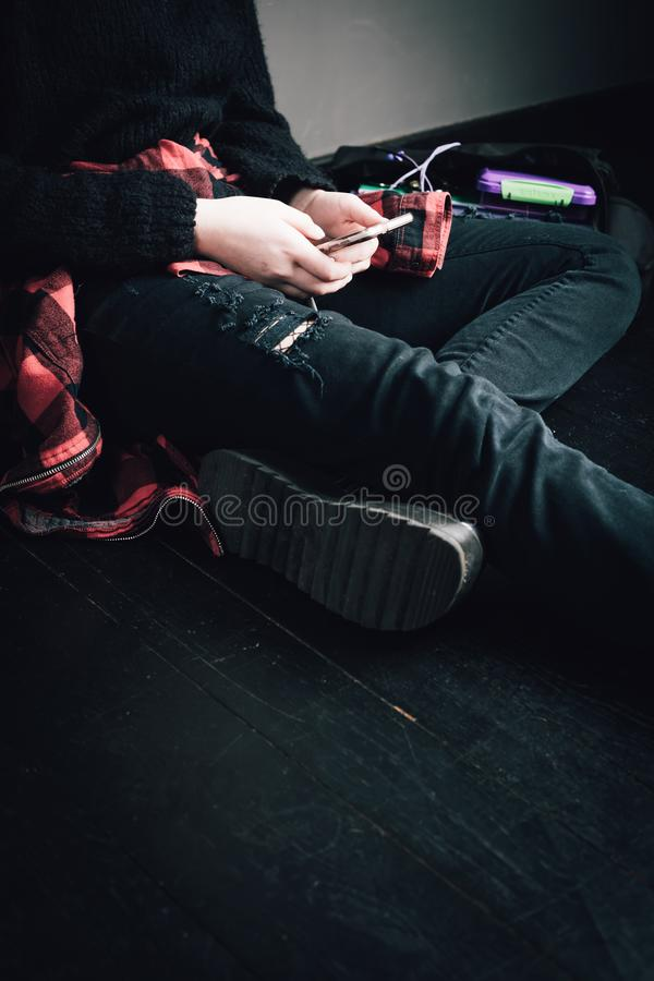 Young alternative girl sitting on the black floor with a school. Bag, smartphone, sunglasses and headphones. Education, alternative life style, modern life royalty free stock images