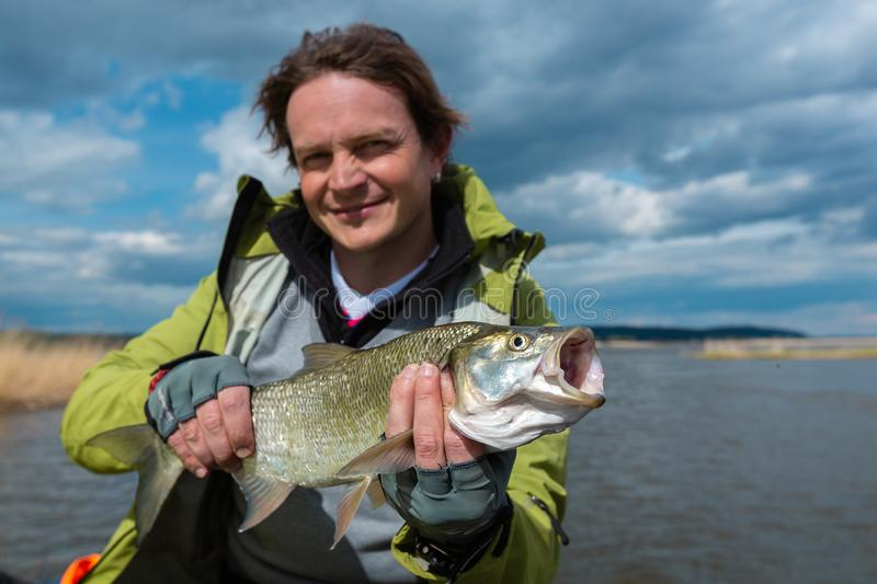 Young amateur angler hold the Asp fish. Aspius aspius with lake on the background royalty free stock photo
