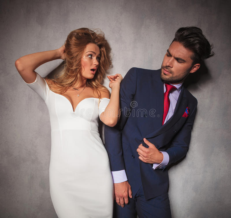 Young amazed elegant woman is looking at her man stock photo