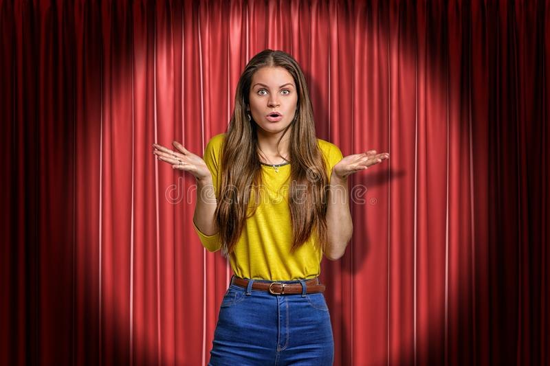 Young amazed, surprised girl wearing jeans and yellow shirt on red stage curtains background stock image