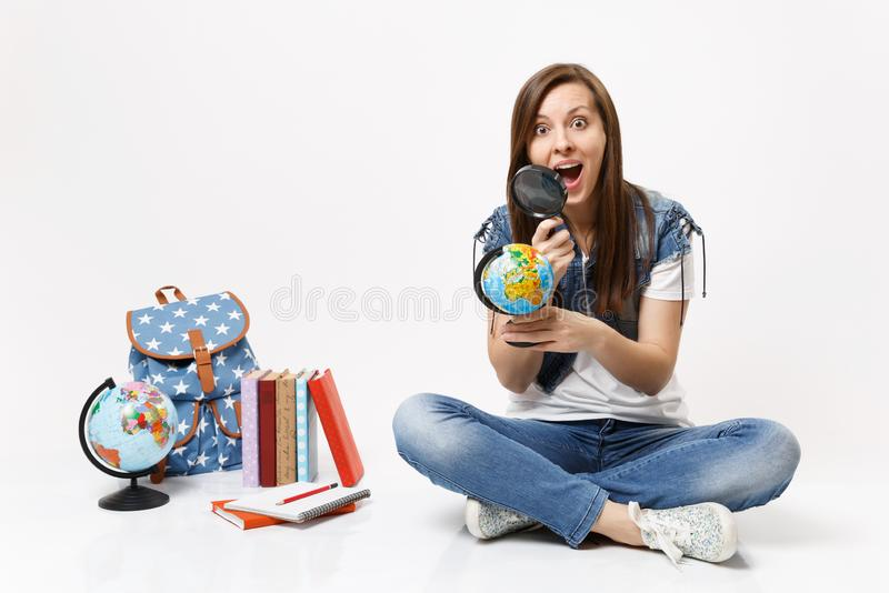 Young amazed surprised woman student looking on globe using magnifying glass learning sitting near backpack, school. Books isolated on white background stock image