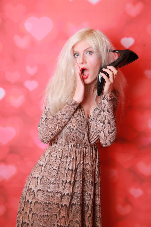 Young amazed woman using a shoe like a telephone holding it near her face and talking, red background. Pin-up style. stock image