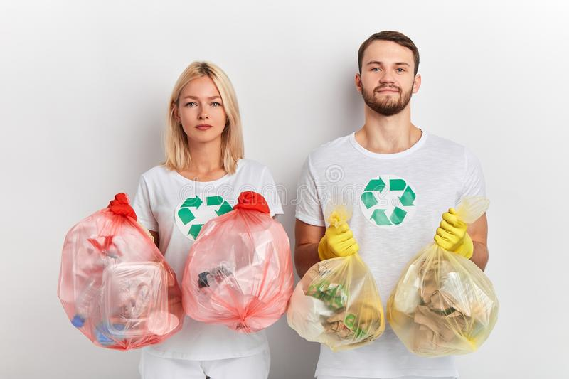 Young ambitious people taking care of environment. Close up portrait, global problem, isolated white background, good tradition.the solution to this pollution stock photos