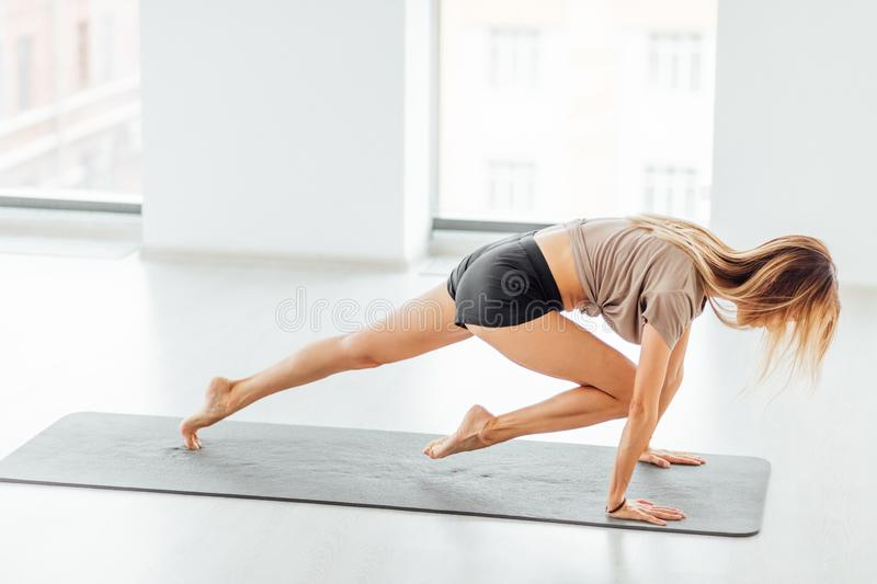 Young ambitious sportswoman doing exercises in the health studio royalty free stock image