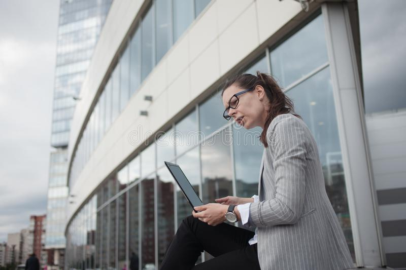 Young ambitious woman with a laptop in her hands on the background of the business center. stock images