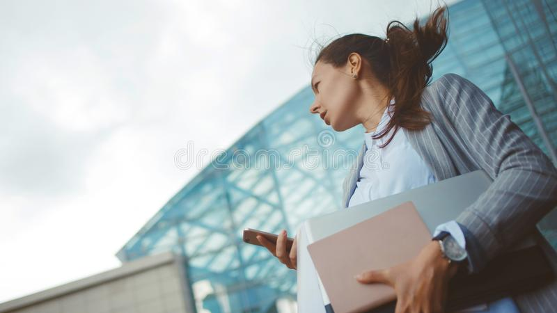 Young ambitious woman with a laptop in her hands on the background of the business center. royalty free stock images