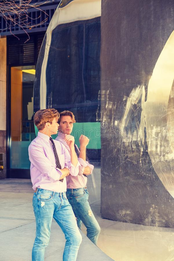 Young American Man looking at mirror. Young American guy in New York, wearing long sleeve, light pink shirt, black, white polkadot tie, jeans, standing against stock photo