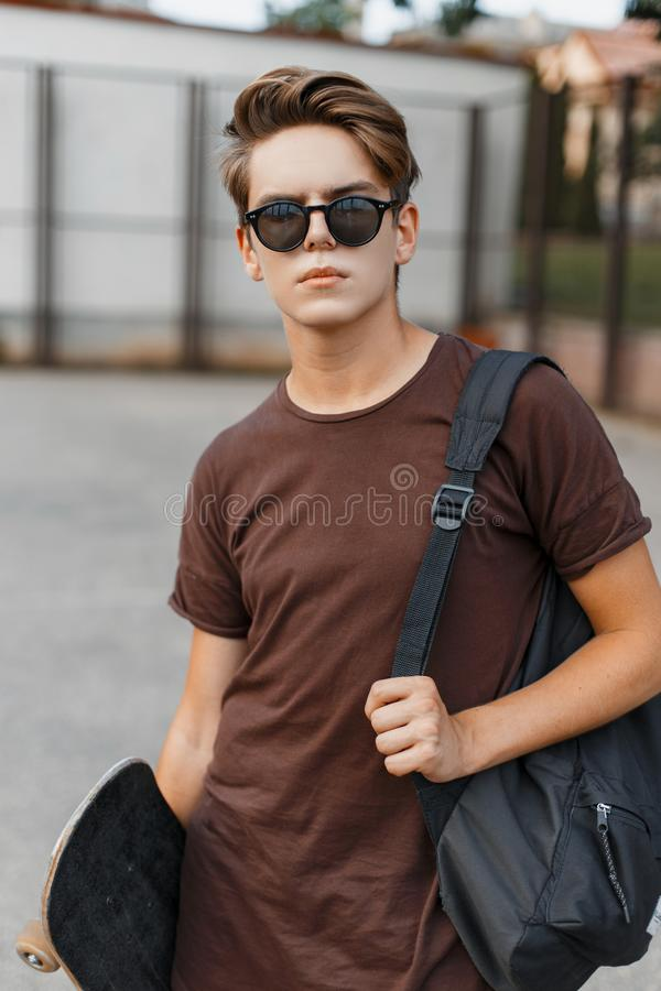Young American hipster man in black trendy sunglasses in a trendy T-shirt with a sports black backpack with a skateboard stock photo