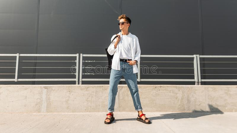 Young American man model in stylish clothes in sunglasses in red leather sandals with a vintage black bag stands. On a bright sunny day near a gray building stock photo