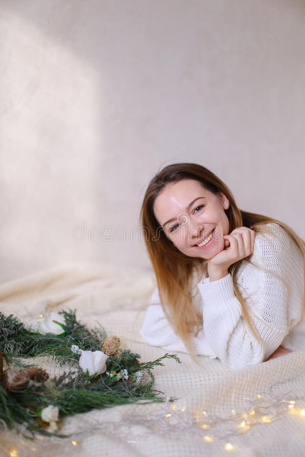 Young american woman lying on bed near green wreath and yellow garlands. Young american girl lying on bed near green wreath and yellow twinkling garlands royalty free stock photo