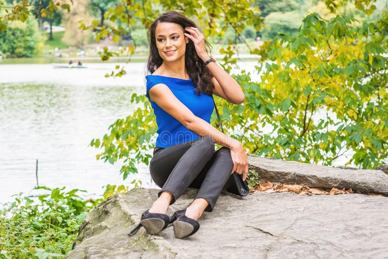 Young American Woman traveling, relaxing at Central Park, New Yo. Rk, wearing blue sleeveless shirt, black pants, high heels, sitting on rocks under green trees stock photography
