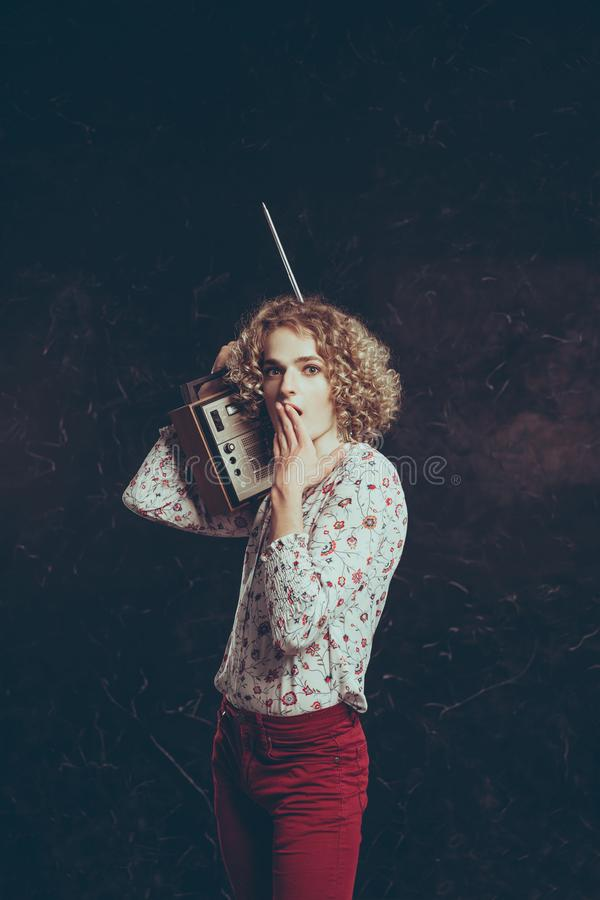 A young androgynous guy in a shirt with flowers is listening to the radio on a vintage radio, in surprise he closed his mouth royalty free stock images