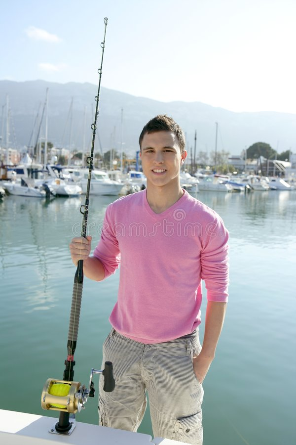Young angler boat fisherman with rod and reel. Over blue water on harbor royalty free stock images