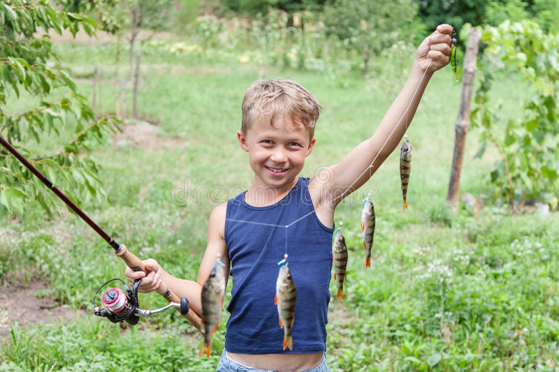 Young angler with tackle perch killer. Young angler with tackle bass killer, fisherman boy with fish perches caught on spinning with instantaneous reel stock photography