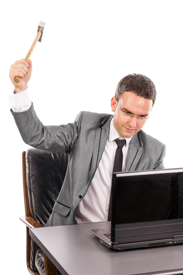 Young angry business man with a hammer smashing a laptop royalty free stock image