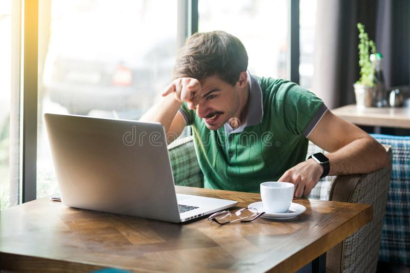 Young angry businessman in green t-shirt sitting and looking at laptop display with crazy face and horns gesture on his forehead. Business and freelancing stock image
