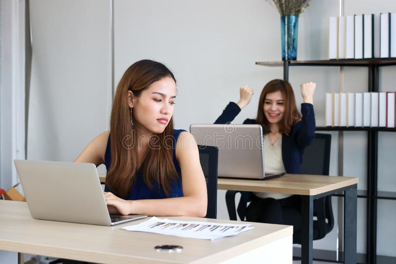 Young angry envious Asian business woman looking successful competitor colleague in office stock photo