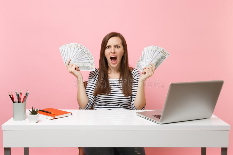 Young angry irritated woman scream spread hands with bundle lots of dollars cash money work at office at white desk with. Pc laptop isolated on pink background royalty free stock photos