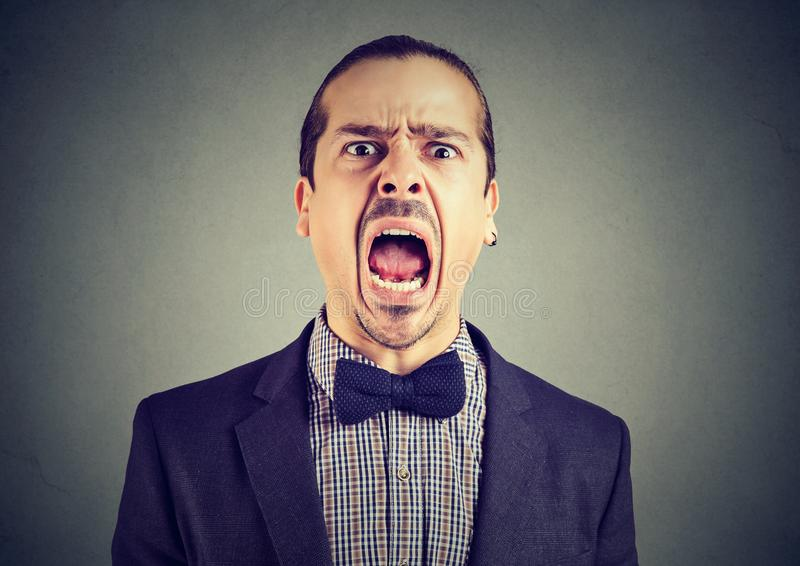 Young angry man screaming with wide open mouth royalty free stock photography
