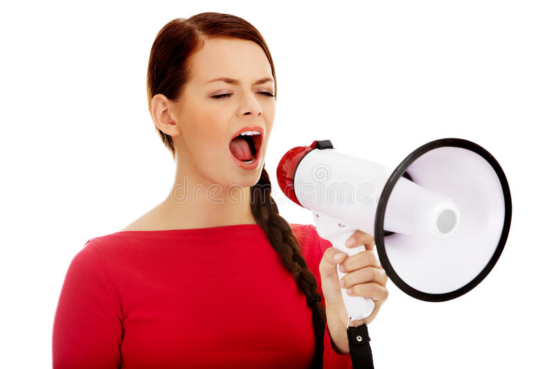 Young angry woman screaming through a megaphone stock image