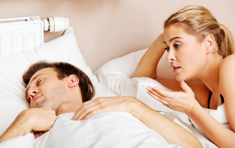 Young angry woman talking to her sleeping husband. Young angry women talking to her sleeping husband royalty free stock photos