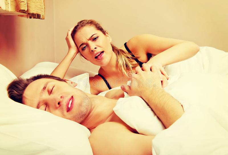 Young angry woman talking to her sleeping husband. Young angry women talking to her sleeping husband stock image