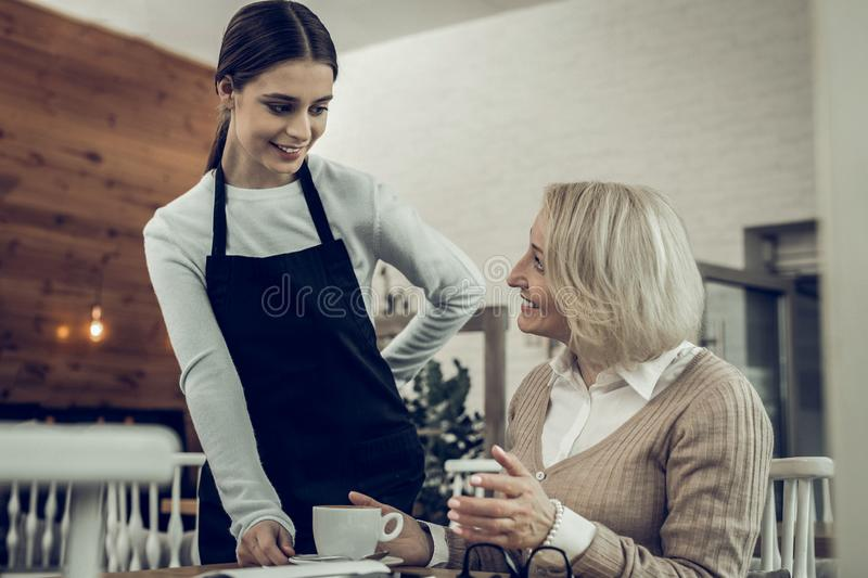 Young appealing waitress communicating with her client. Communicating with client. Young appealing waitress wearing uniform communicating with her client royalty free stock photography