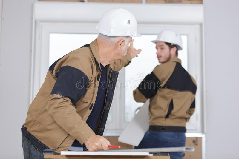 Young apprentice helping in window installation stock photography