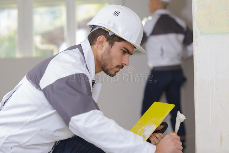 Young apprentice plasterer working on indoor wall royalty free stock photo