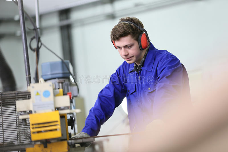 Young apprentice working in metallurgy workshop royalty free stock photo