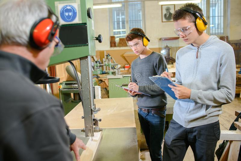 Young apprentices protecting ears from noisy machinery royalty free stock images