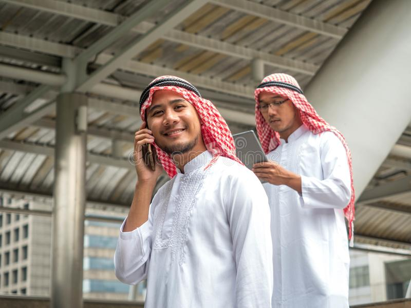 Young Arab businessman talk through smartphone lifestyle concept. Muslim businessmen talking mobile phones royalty free stock photography